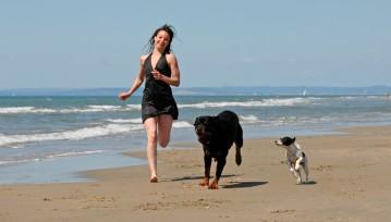 mujer corriendo con sus perros junto a la playa de arenas blancas
